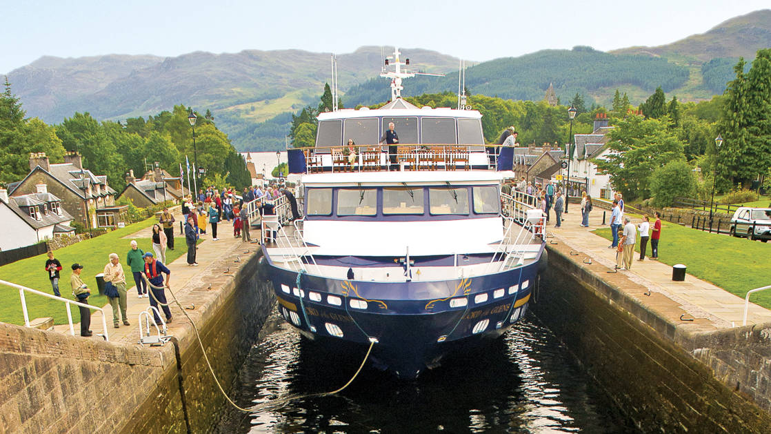 Small ship Lord of the Glens transiting the Caledonia Canal in Scotland with people watching