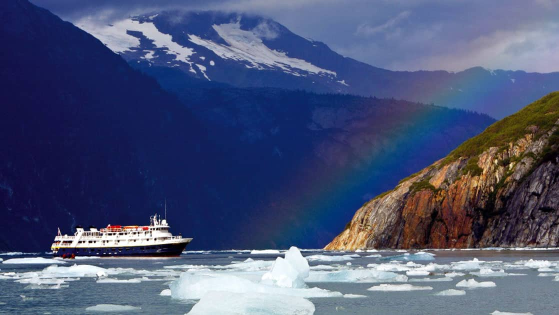 National Geographic Sea Bird among ice bergs in remote Endicott Arm in Alaska with a rainbow.