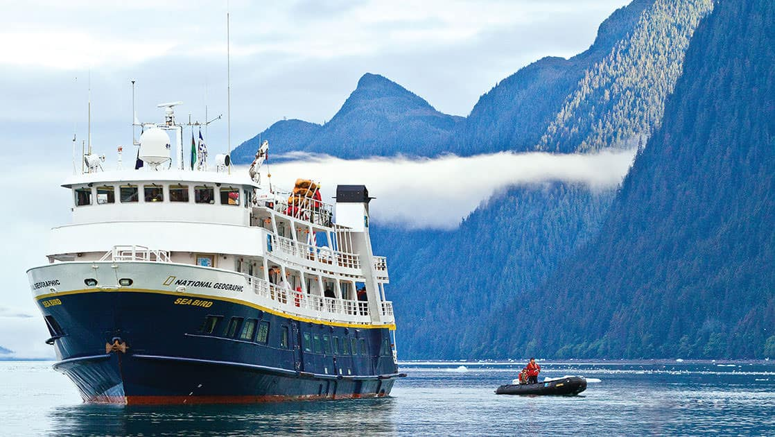 The National Geographic Sea Bird small expedition ship in the misty fjords of Alaska with a small inflatable skiff next to it.