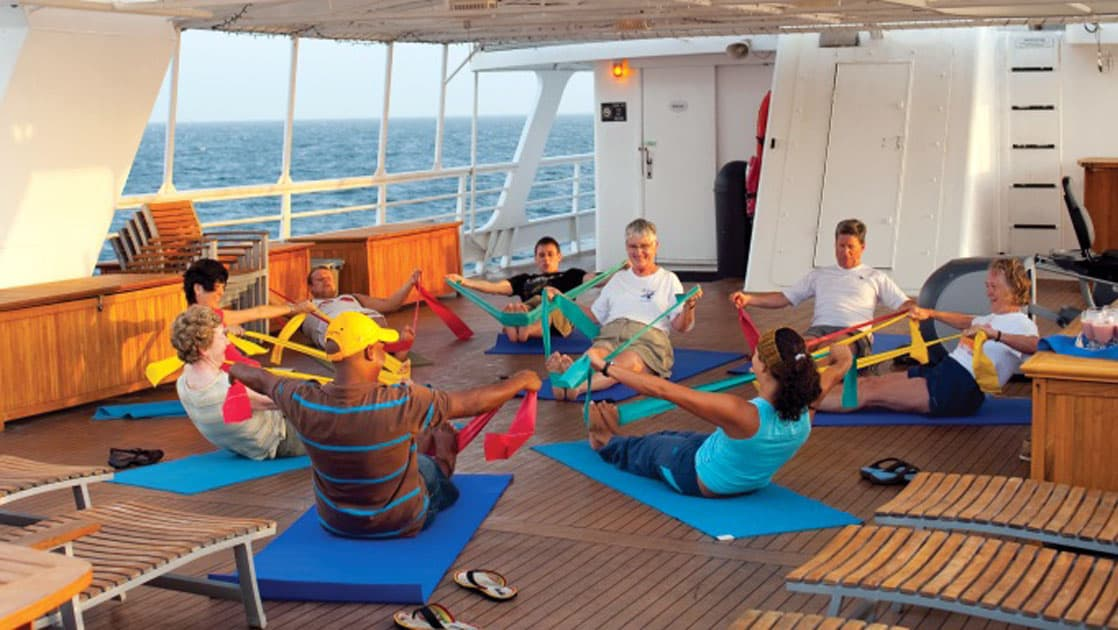 Yoga instructor leads guest in stretching exercise on sunny deck of National Geographic Sea Lion small ship