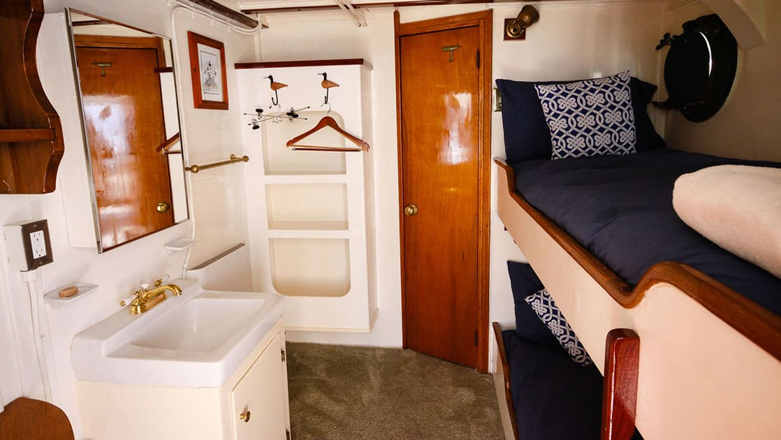 Twin bunk beds, sink, mirror, porthole in Stateroom 6 aboard Sea Wolf yacht in Alaska