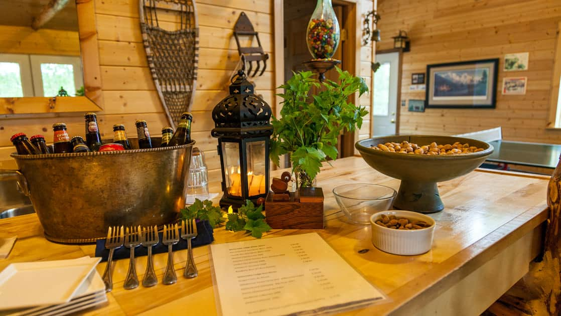 Alaskan-brewed beers are served in a metal bowl next to other snacks inside the dining room at Winterlake Lodge, an Alaska wilderness resort
