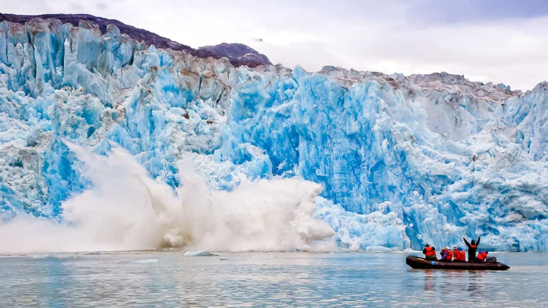 Small ship cruise passengers explore on Zodiac in Tracy Arm, Alaska with calving ice