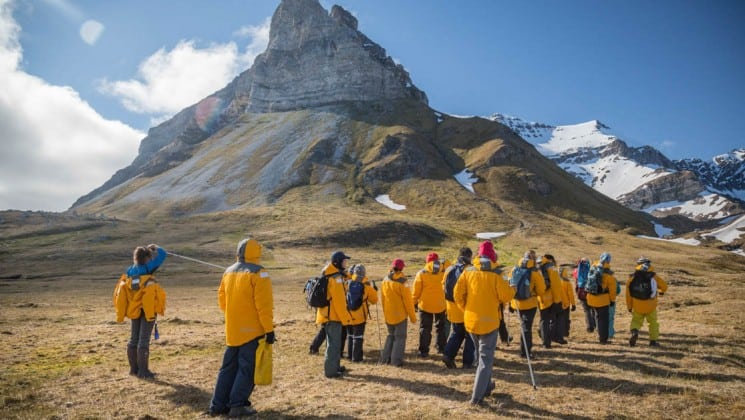 group of hikers surrounded by arctic landscape in spitsbergen