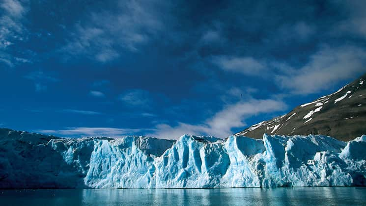 an illuminated iceberg sticking out of calm water on a sunny day on the spitsbergen in depth small ship arctic cruise