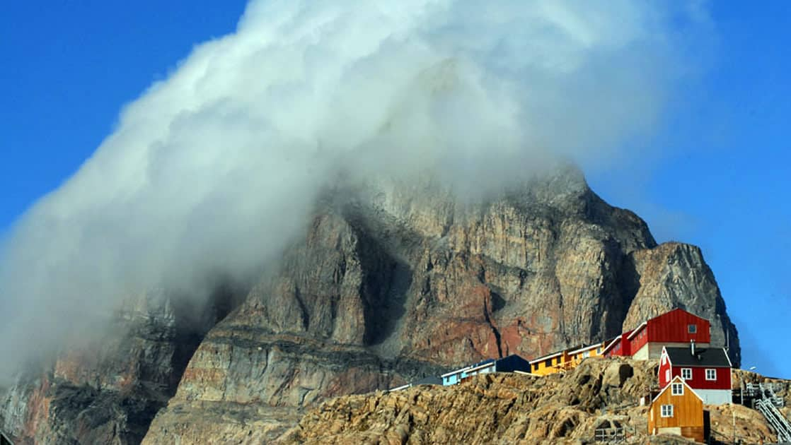 fog rising above a mountain with a small colorful arctic village next to it on a sunny day