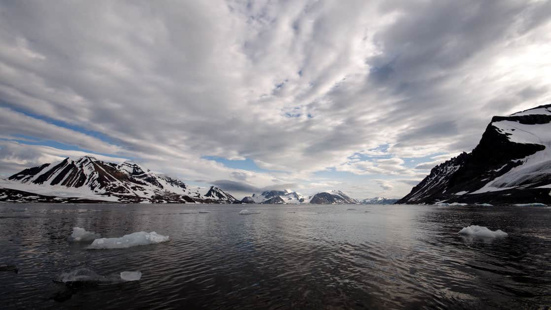 looking over dark ocean water with ice floating on it and snowy mountains on either side and clouds above on the spitsbergen in depth small ship arctic cruise