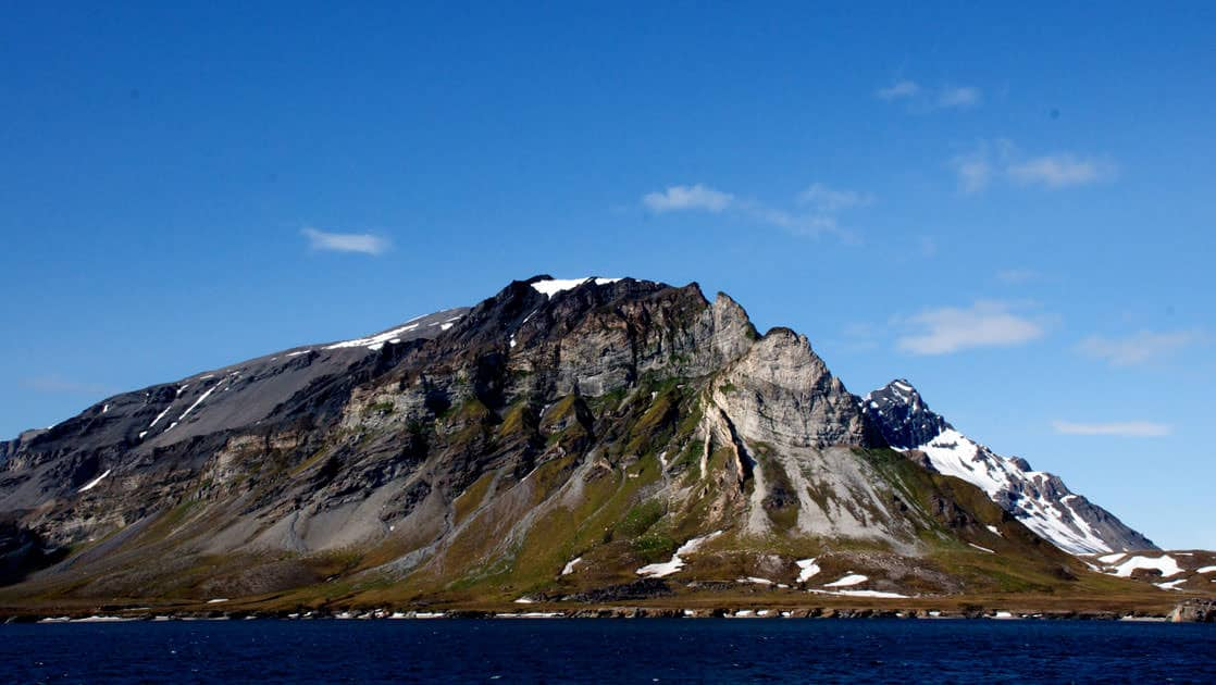 a mountain jutting out of the ocean with green tundra at the base on a sunny day in spitsbergen arctic