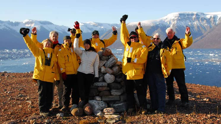 group of adventure travelers in yellow jackets grouped together throwing their hands in the air on a sunny day with the arctic ocean and mountains in the distance