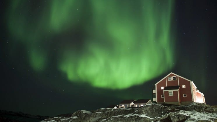 small house on a hilltop with the green arctic aurora borealis behind it