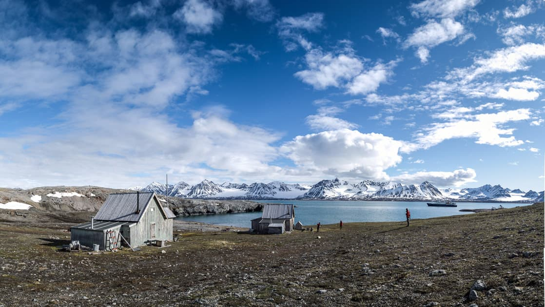 small arctic coastal fishing village on a partly cloudy day with mountains in the distance