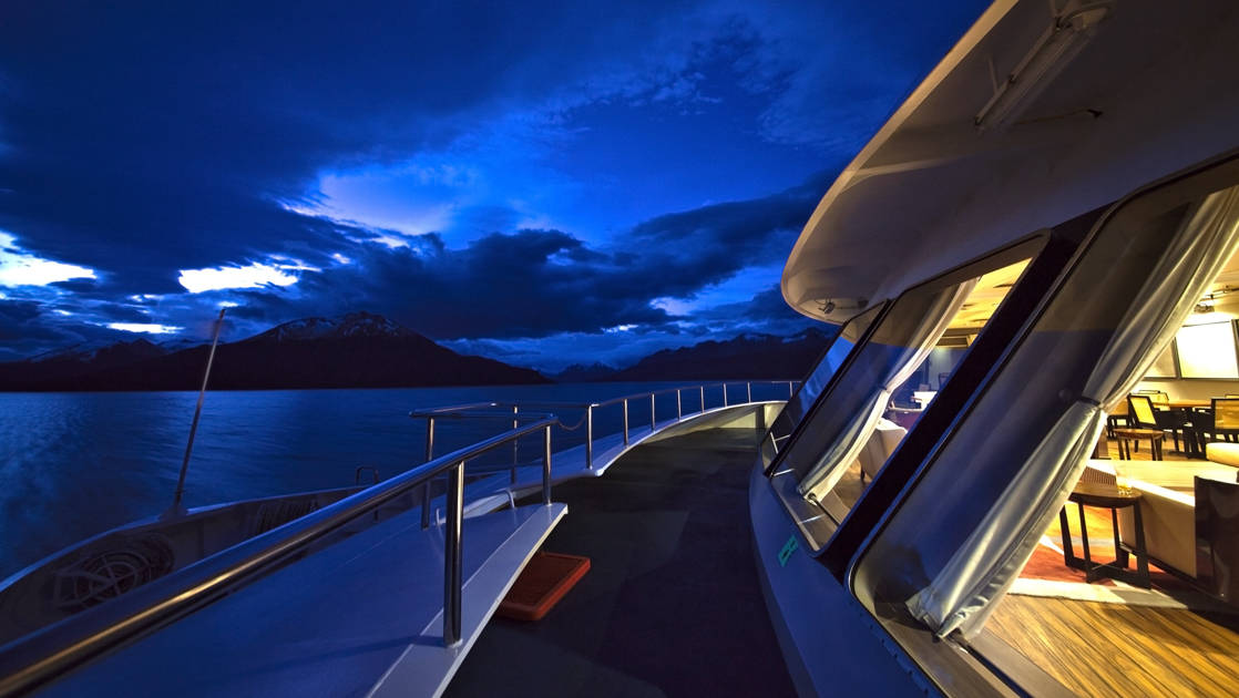 Outside the lounge on deck near the bow of Stella Australis during the evening.
