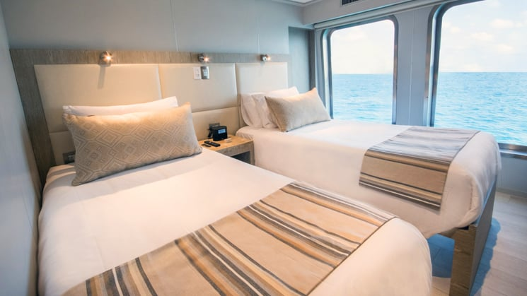 origin and theory luxury ship cabin with 2 twin beds with an ocean view