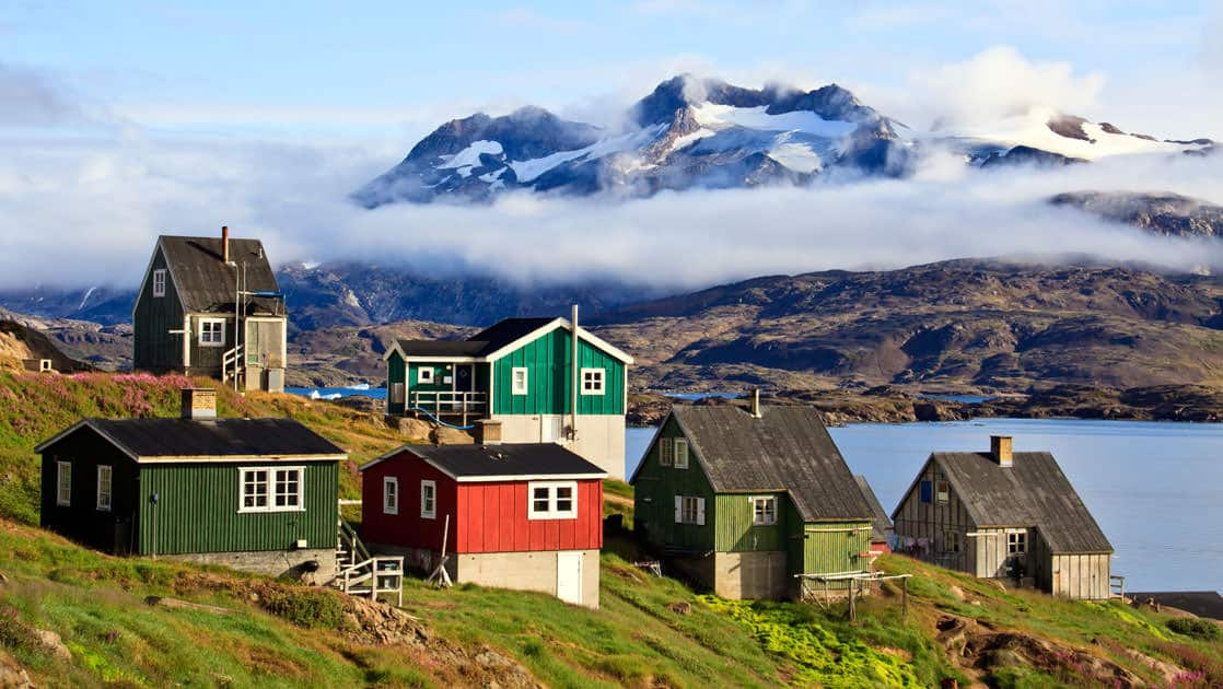 a group of small colorful houses on a hillside in greenland with the sea and large mountains in the background
