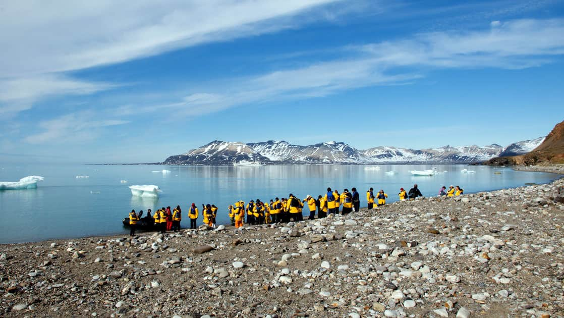 travelers stand on the arctic shore where there is a zodiac inflatable skiff waiting to take them back to the small ship
