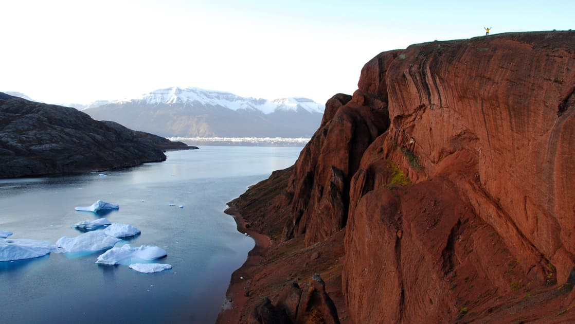 red cliffs with icebergs below seen on the three arctic islands iceland, greenland, spitsbergen small ship cruise