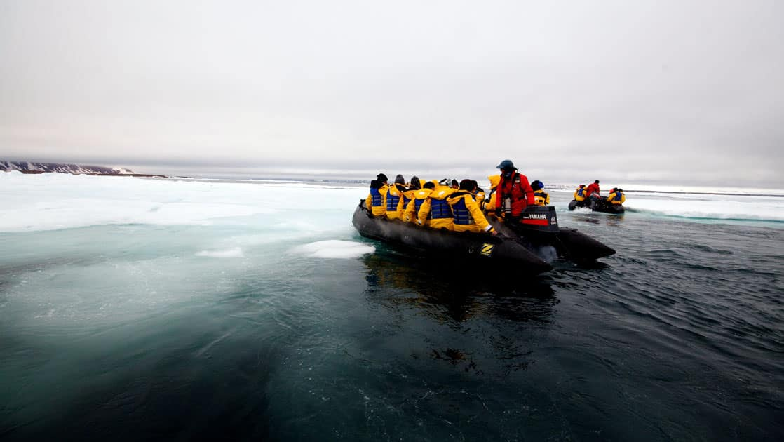 adventure travelers on the three arctic islands iceland, greenland, spitsbergen small ship cruise take a zodiac over calm waters with ice underneath