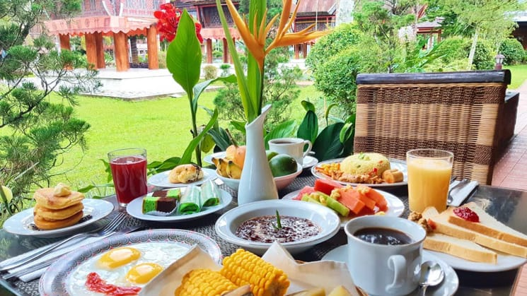 A table with a full breakfast layout at Toraja Misilliana Hotel.