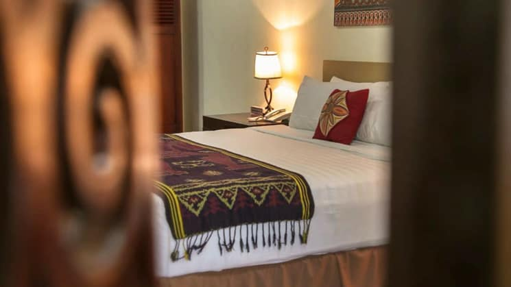 A peek into a room at Toraja Misilliana Hotel with a queen bed and colorful woven bed throw on white bed.