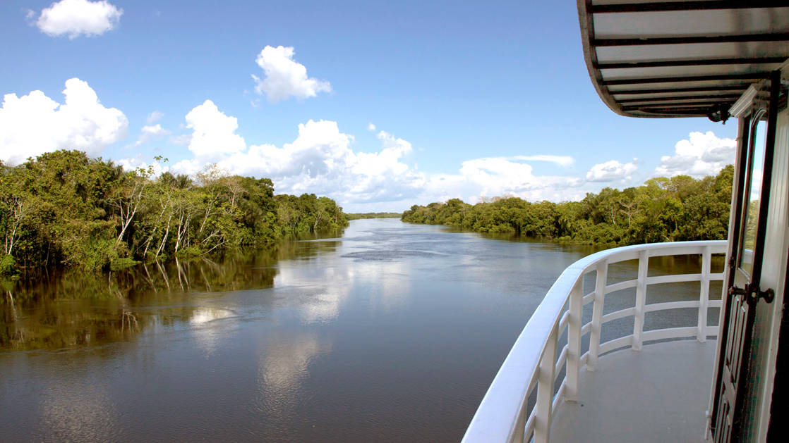 view from a deck of the tucano river boat as it cruises down the rio negro, brazil
