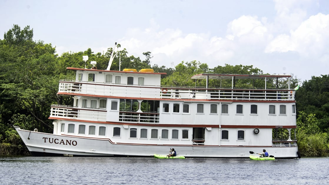 Port Side of small river boat Tucano in the Amazon with tho kayakers approaching.