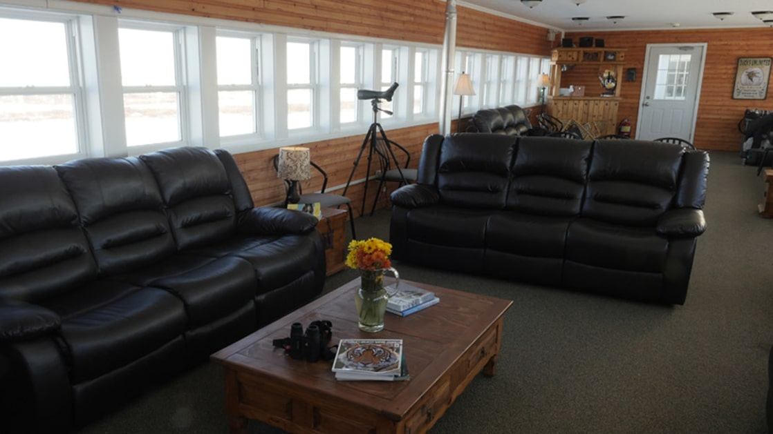 Two leather sofas, binoculars and a coffee table in the Tundra Lodge lounge with windows overlooking the Canadian Arctic.
