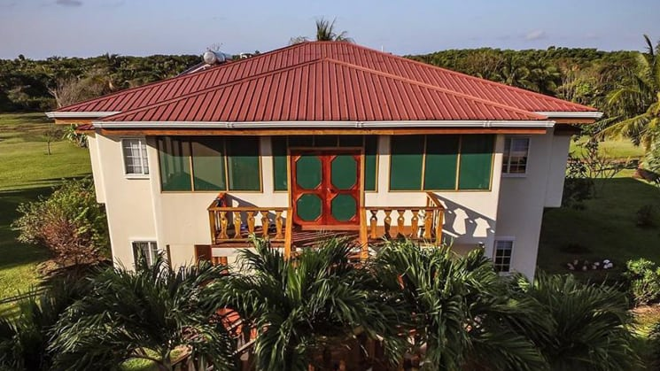 The Garden Villa at Turneffe Flats with red roof and small porch on second floor.