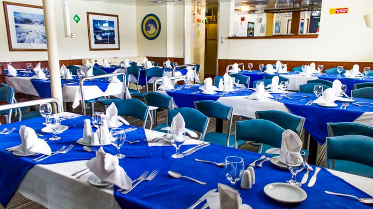 Ushuaia dining room with blue tableclothes and table set with wine glasses and plates.