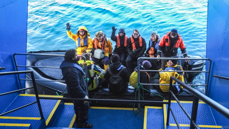 Ushuaia inflatable skiff loading off the side of ship with a group full of people in life vests.