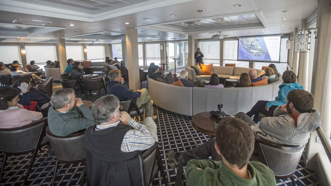 Lecture lounge area with projector screen aboard Ventus Australis.