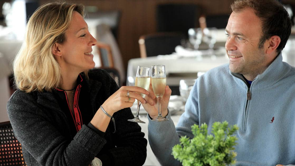 Man and woman cheers their champagne glasses in the dining room aboard Ventus Australis.