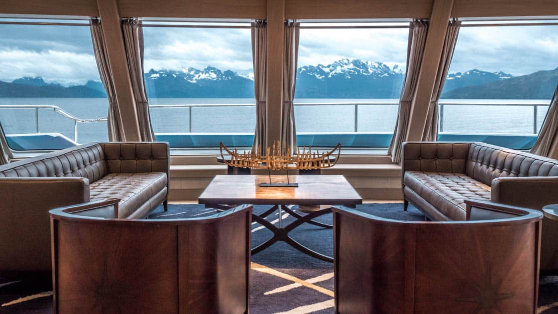 Two sofas and two chairs around a coffee table by windows in the lounge aboard Ventus Australis with views of the mountains out the windows.
