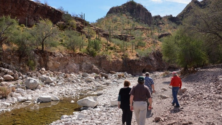 group hiking along creek in baja on westward voyages small ship cruise