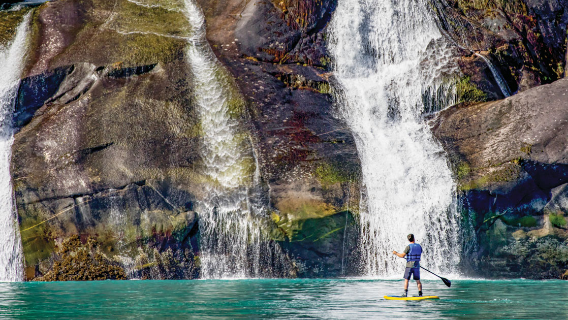 Man stands atop a paddleboard in turquoise water in front of tall waterfalls cascading over a large rock cliff wall in Alaska.