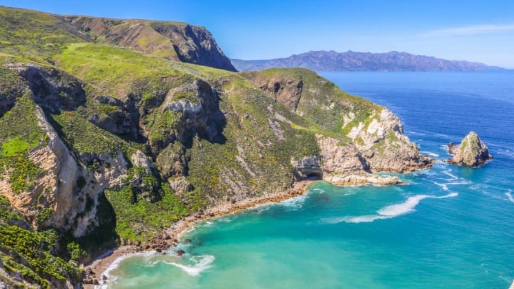 aerial of secluded bay with turquoise water and large cliffs in channel islands