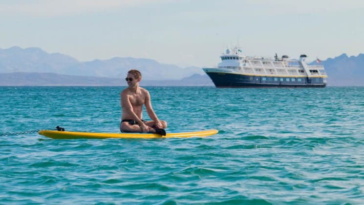 man on paddleboard off port bow of wild california escape: channel islands cruise ship
