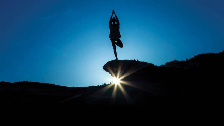 performing yoga on cliff at sunrise on wild california escape: channel islands cruise