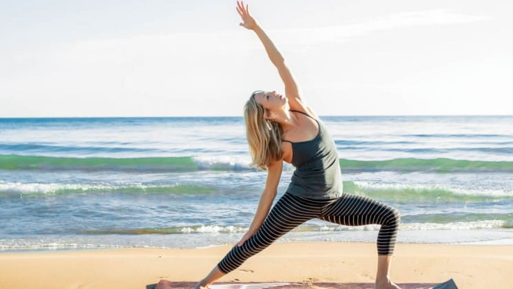 woman doing yoga on beach in channel islands