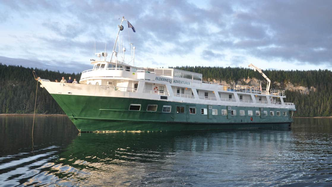 Portside exterior view of the Wilderness Adventurer cruising in Alaska during sunset.
