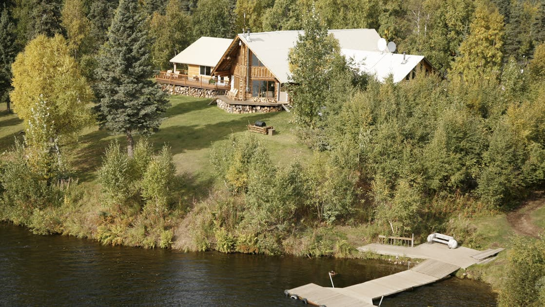 An aerial view of the Winterlake Lodge, located next to the water and situated in the Alaskan forest, with a private dock.