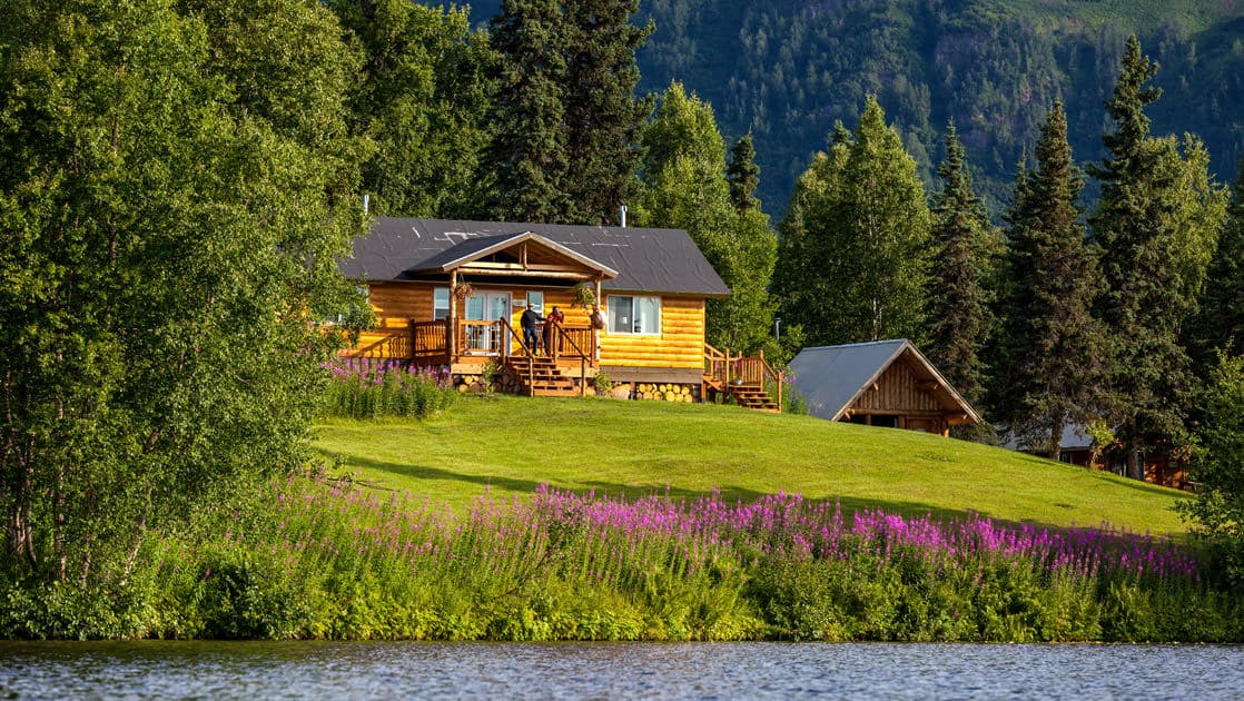 The Winterlake Lodge is perched on a grassy knoll above flowers and water, with pine trees in the background, in Alaska