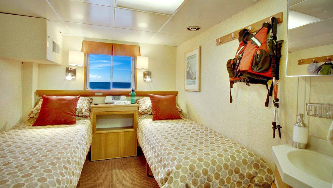 Trailblazer cabin with twin beds and window aboard Wilderness Discoverer