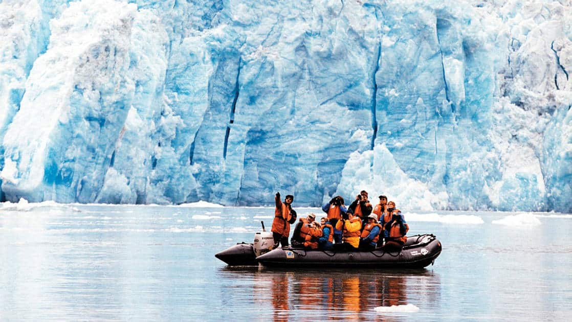 Small ship cruise passengers on a skiff in front of a glacier in Alaska pointing out site and looking through bincoluars