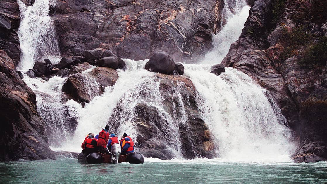 Small ship cruise guests on an inflatable skiff excursion getting up close to waterfalls in the fjords of ALaska