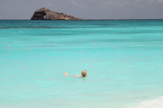 Guest from a small ship cruise in the Galapagos floating in the bright turquoise water alone.