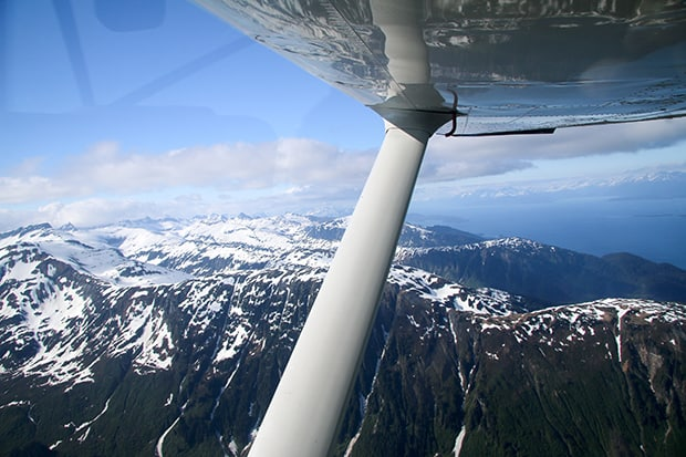 View of snowy mountains and a waterway from a seaplane on the flight to Gustavas Alaska.