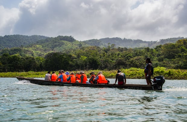 Group of costa rica travelers motoring in a dugout canoe on the Mogue River in Panama.