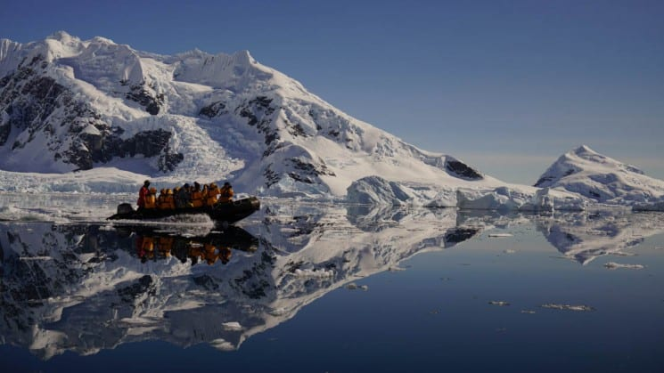 A zodiac boat from Explorers and Kings expedition cruise motors on clear water with icebergs reflecting in antarctica