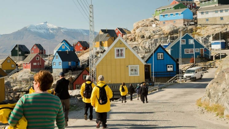 people walk down a street toward colorful houses on a bluff in greenland