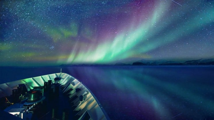 Green and purple northern lights illuminate the sky and reflect in the ocean in front of the ship for the arctic sights cruise